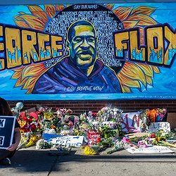 "A colorful mural of George Floyd who was unjustly killed by police in Minneapolis. His face is in the middle with the words George Floyd in large, orange block lettering. the text ""Say our names"" and ""I can breathe now"" is written above and below George's head with the names of fellow Black people who have been killed by police written behind him."
