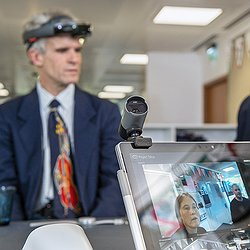 Project Tokyo uses an adapted HoloLens and real-time computer vision to recognize people's faces. This image shows a blind person wearing the HoloLens (augmented reality head-mounted display) and looking at a nearby person's face.