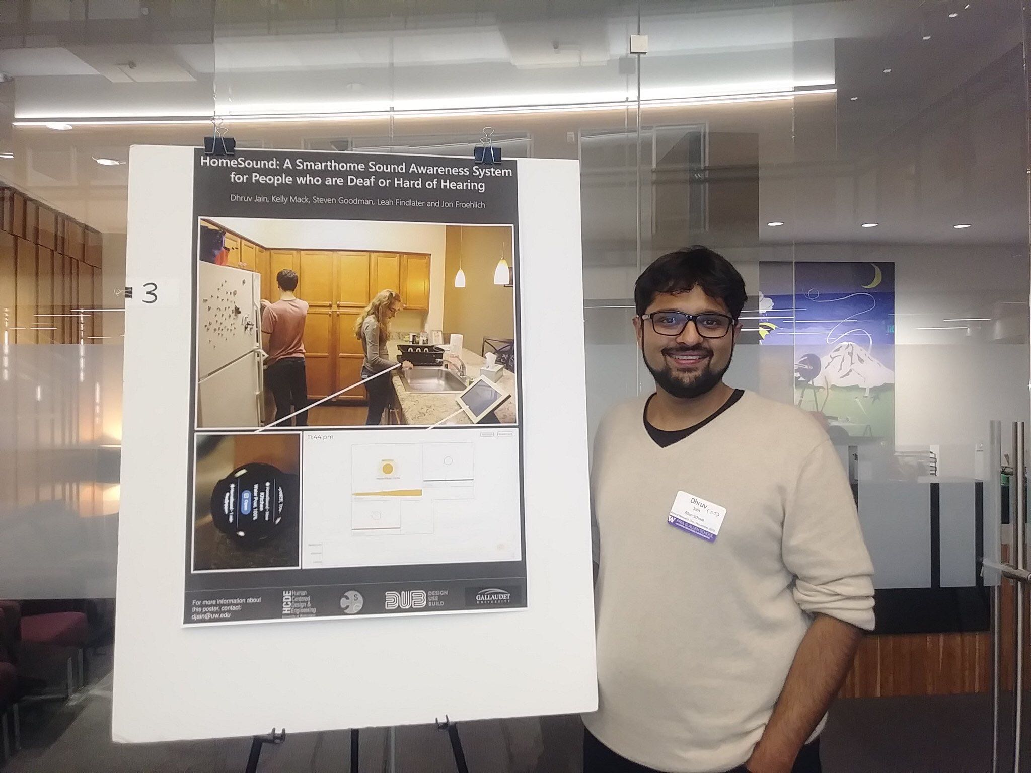 Dhruv standing in front of his award-winning HomeSound poster