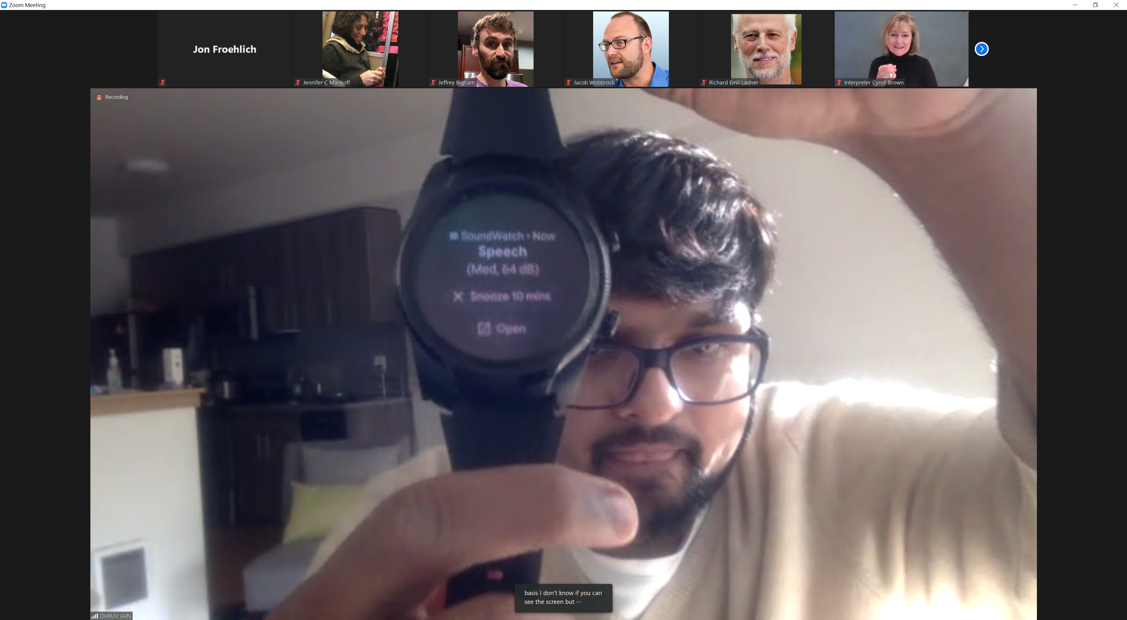 Image shows DJ holding an Android watch running the SoundWatch app, which has inferred that speech is inferring around him and shows this on the display